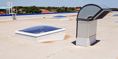 Roof of a commercial building with skylights and exhaust vents.